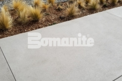 Bomanite Sandscape Refined decorative concrete is featured here and the use of white color hardener paired with locally sourced aggregates, mirror glass, and distinctive saw cuts enriches the nautical themed design at the 50 Fifty DTC office complex.